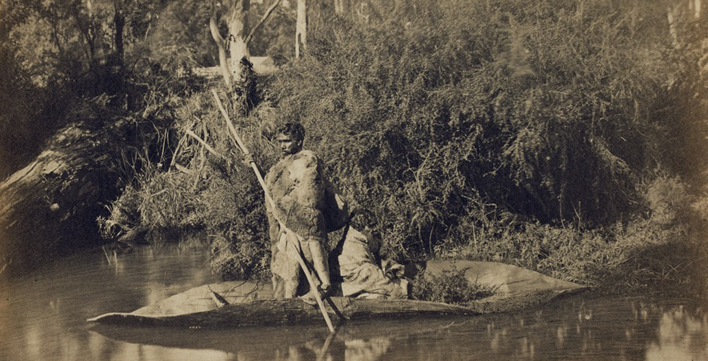 Two men in possum skin cloaks paddle a red gum bark canoe on the Yarra River, Fred Kruger (1870). Image via Culture Victoria.