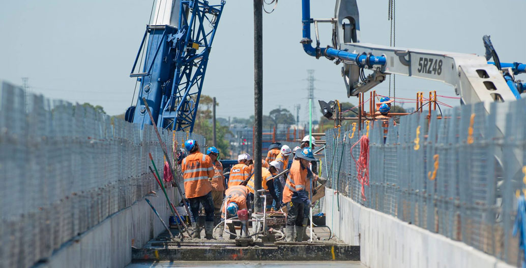 Construction staff pouring concrete for the elevated rail deck. Image: LXRA.