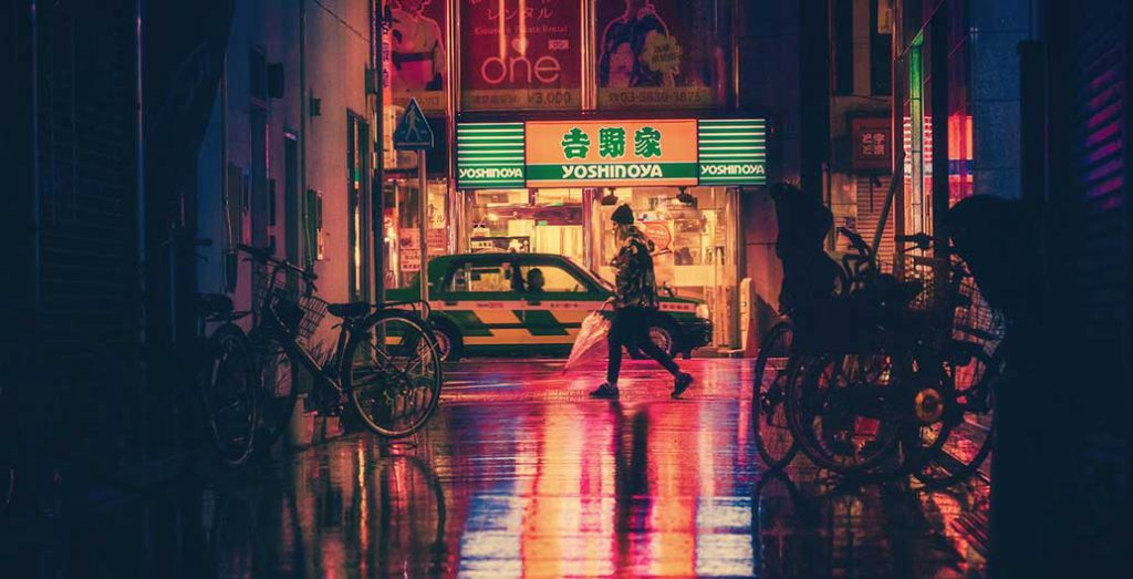 A woman walking in a night street in Japan.