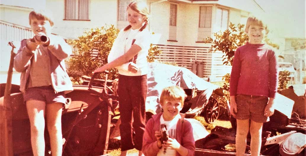 Walsh was brought up in Townsville, with a free-form yard. Here playing in 'Dad's vintage car collection'.