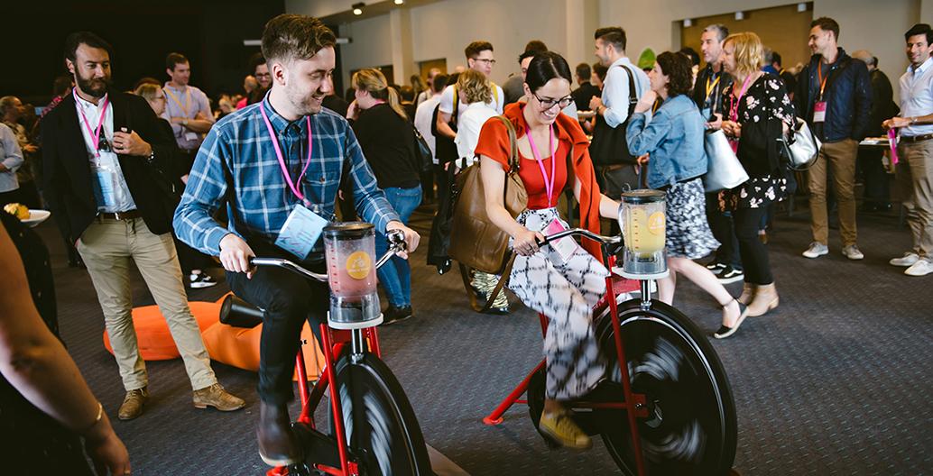"""Conference delegates """"biking"""" a smoothie at the WE-EF """"Bike'n'Blend"""" station"""
