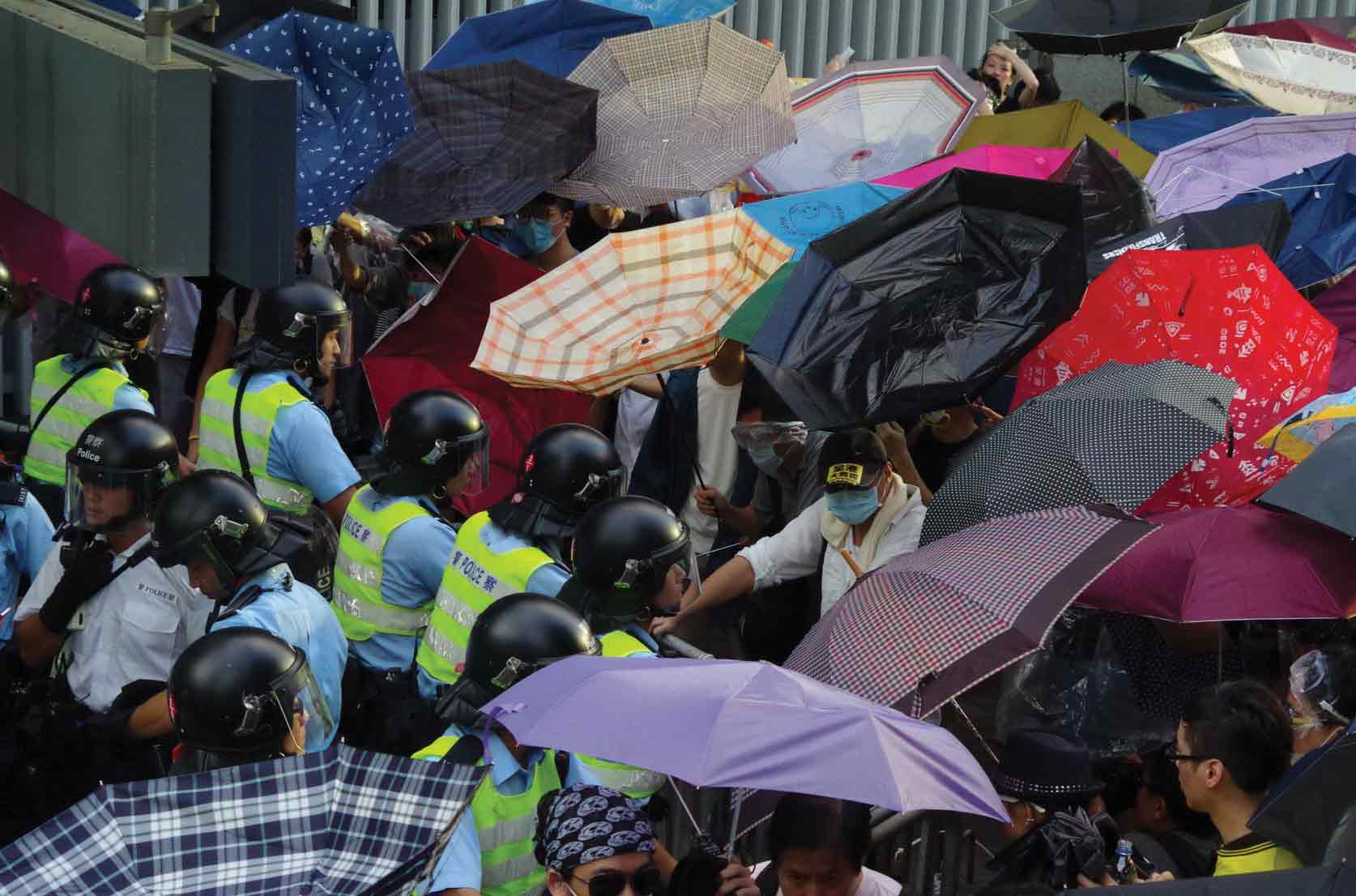 Protesters using umbrellas as shields from the police and later, tear gas, 2014. Photo: FX Pasquier
