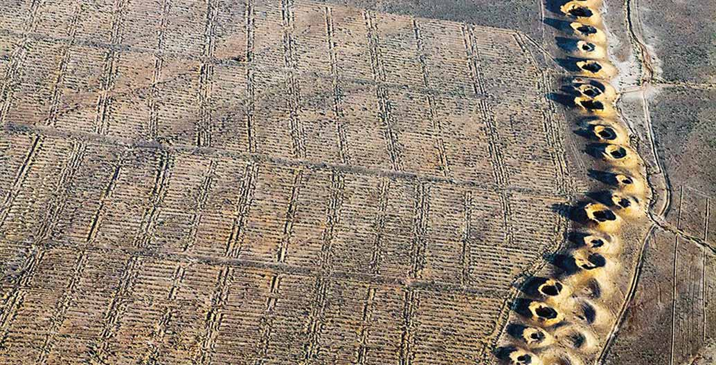 A line of evenly spaced spoil craters in Iraq is the only evidence of a subterranean man-made water stream called a qanat, first constructed by the Persians during the early years of the first millennium BCE. Photo: © Alireza Teimoury