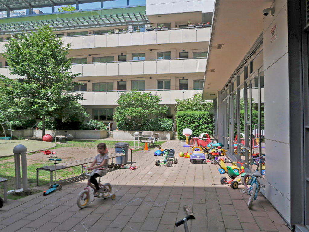 Children playing in a residential courtyard with scattered shared toys, Vancouver.