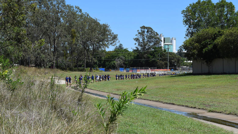 Students from a nearby school walk Small Creek's old concrete channel. Image: Courtesy Amalie Wright